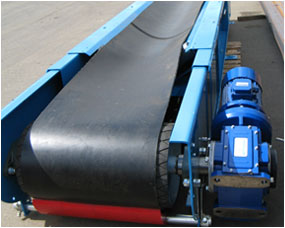 Heavy duty conveyor with rubber lagged drive drum and belt scraper