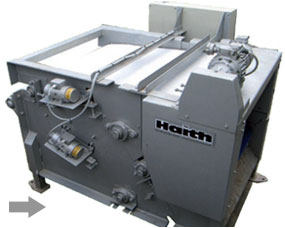 Multi roller belt press with cleaning brush system and belt vibration for improved de-watering
